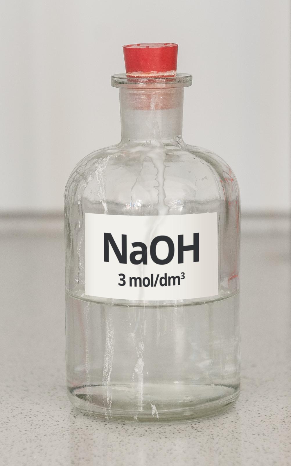 Zdjęcie przedstawia butelkę zprzezroczystego szkła wypełnioną do połowy przezroczystym roztworem. Butelka ma czerwony korek ztworzywa sztucznego ibiałą etykietkę znapisem NaOH, 3 mole na decymetr sześcienny. Na zewnętrznych ściankach butelki znajdują się liczne podłużne smugi białego osadu.