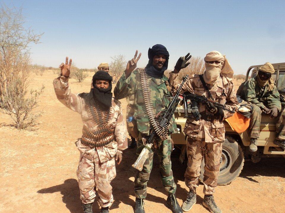 Na zdjęciu uzbrojeni mężczyźni, ztyłu samochód terenowy.