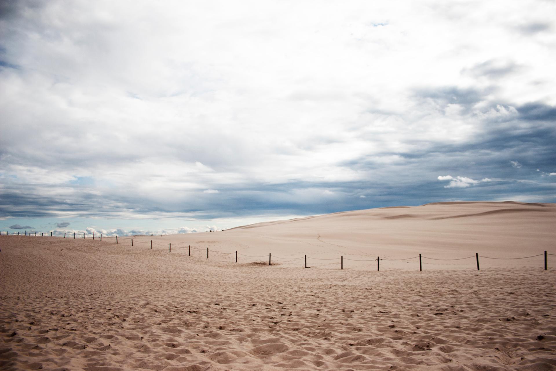 Fotografia przedstawia piaszczyste wydmy pod zachmurzonym niebem. To ruchome wydmy wSłowińskim Parku Narodowym. Przez wydmy biegnie ogrodzenie zpalików.