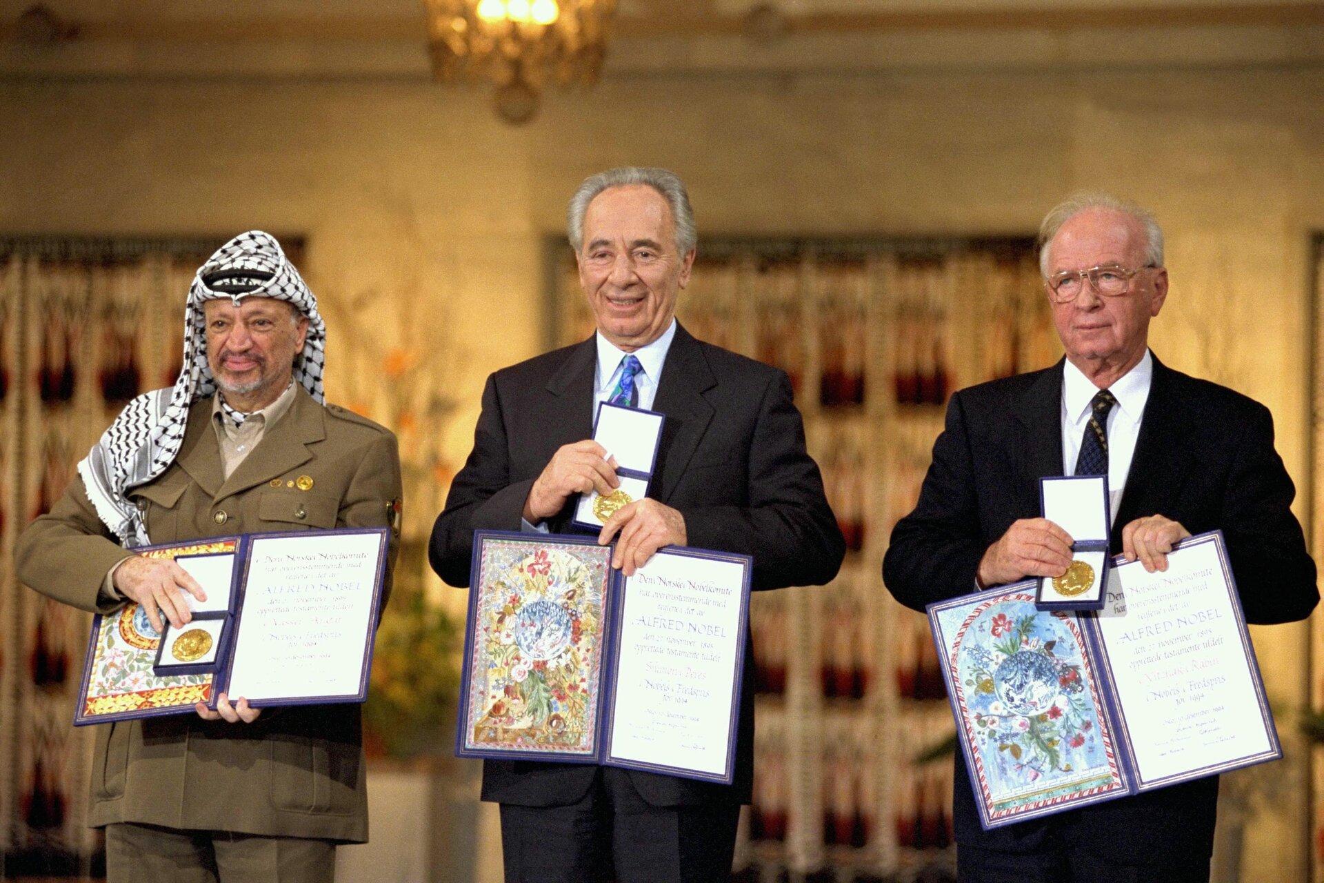Na zdjęciu trzej mężczyźni, jeden wmundurze ichuście na głowie, dwaj wgarniturach. Pokazują medale idyplomy.