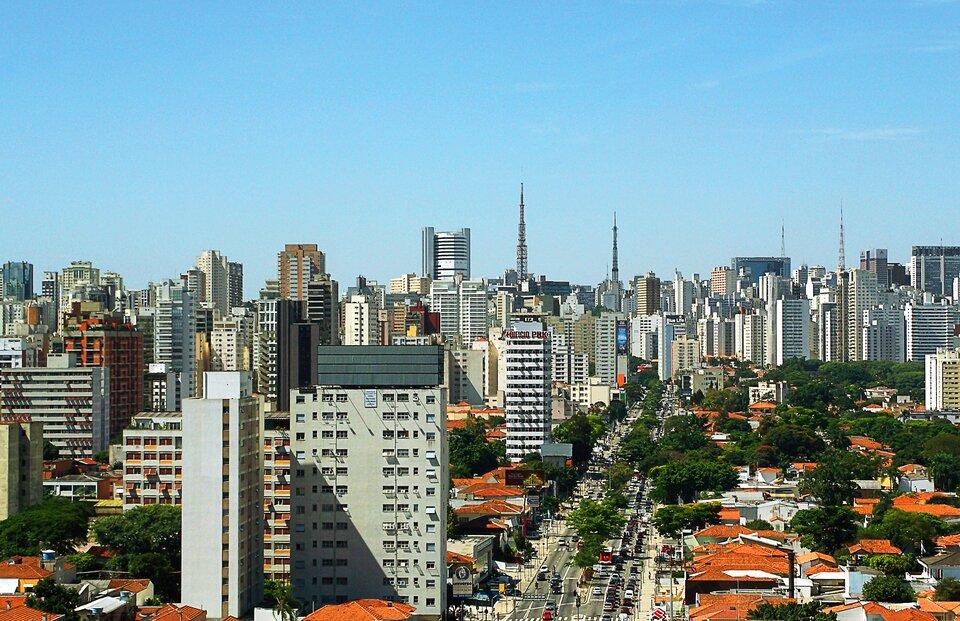 Na zdjęciu lotniczym widok na gęsto zabudowane nowoczesne miasto. Różne typy zabudowy, wysokie wieżowce, niskie domy zczerwonymi dachami. Przez środek prowadzi szeroka ulica.