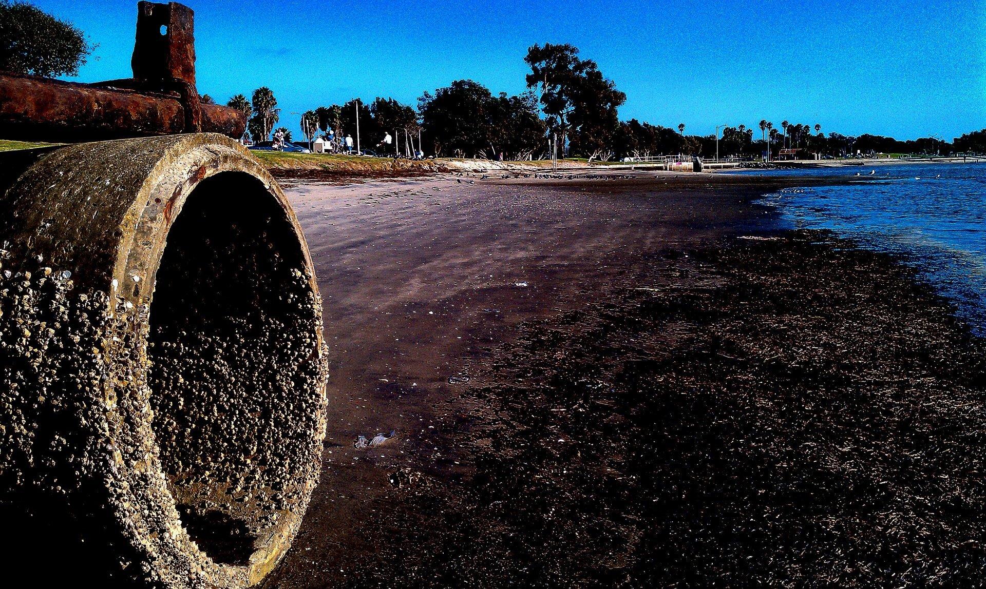 Zdjęcie przedstawia plażę miasta wciepłej strefie klimatycznej po odpływie. Niebo pogodne iniebieskie. Piasek wcentralnej części kadru jest brudnobrązowy zwyraźnymi zanieczyszczeniami, morze mocno cofnięte wprawo. Wtle po lewej stronie zabudowania, wcentrum ipo prawej stronie drzewa izatoka. Na pierwszym planie po lewej stronie obrośnięta naciekami pusta rura kanalizacyjna wychodząca głęboko wplażę.
