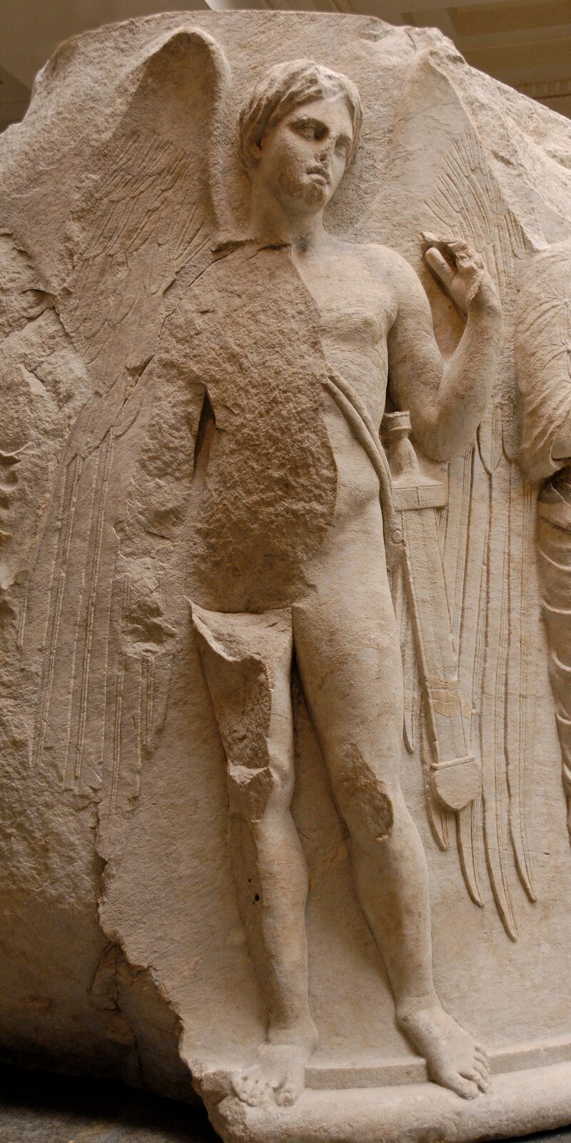 Zdjęcie przedstawia rzeźbę półnagiego mężczyzny. Mężczyzna stoi dumnie zuniesioną lewą ręką. Na biodrze ma pas zmieczem. Zza pleców widoczne są jego ogromne skrzydła.