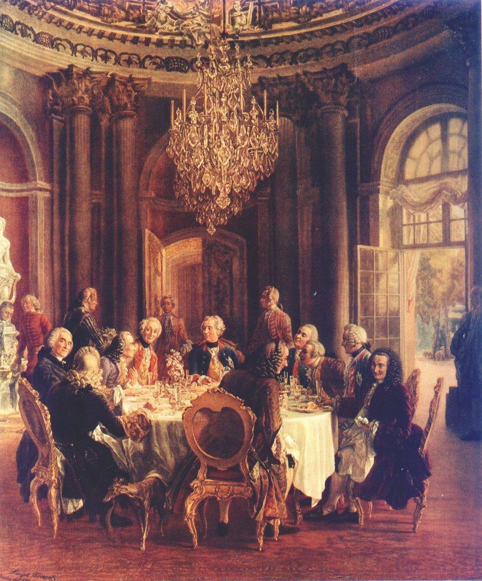 """Okrągły stół ukróla Fryderyka II Wśródnamalowanych postaciznajduje się Wolter (siedzi po lewej stronie, patrzy """"w stronę widza""""). Źródło: Adolph von Menzel, Okrągły stół ukróla Fryderyka II, 1850, olej na płótnie, domena publiczna."""