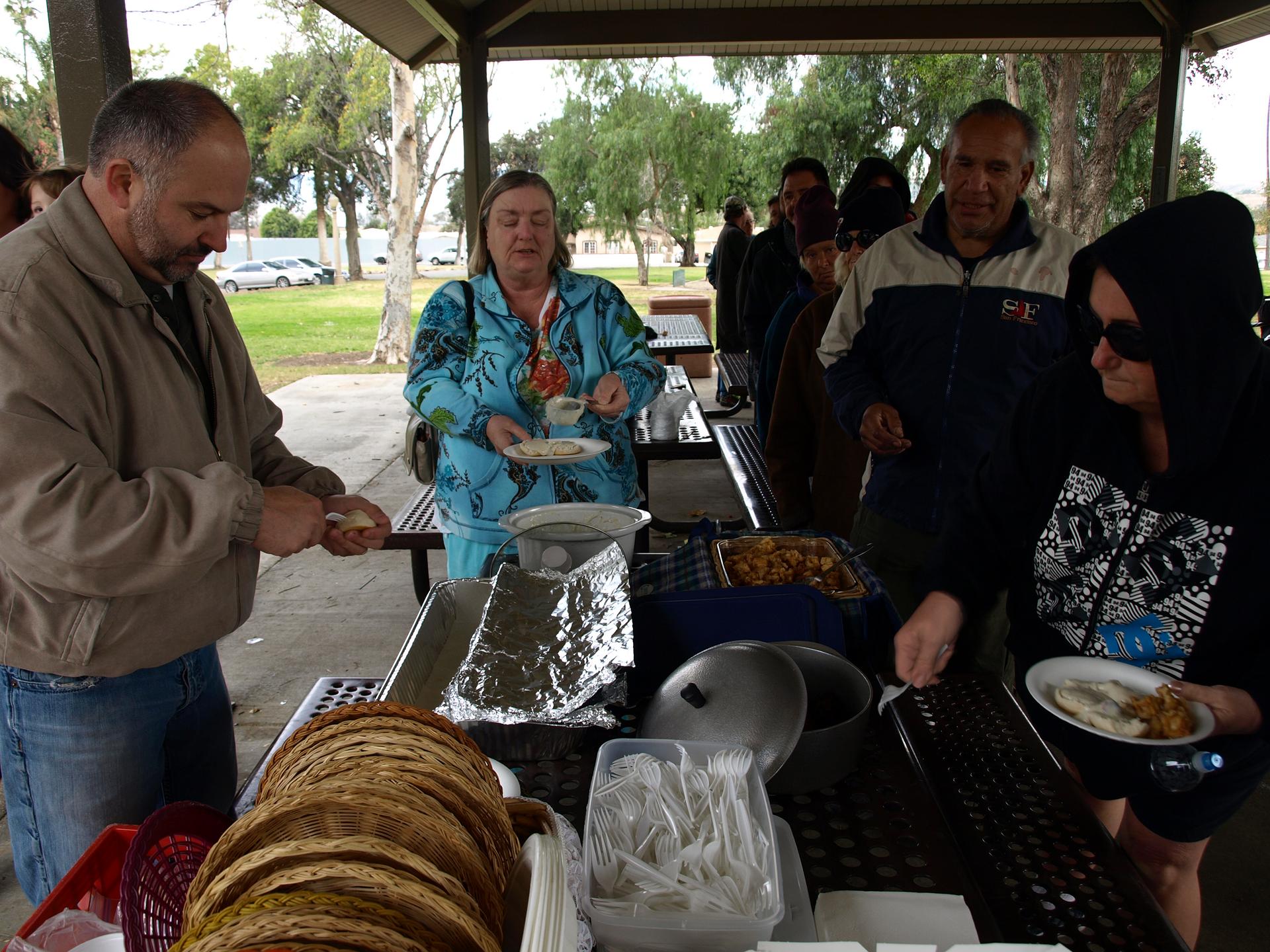 Galeria 1 składa się zdwóch zdjęć. Zdjęcie po prawej. Słoneczny dzień wparku. Kuchnia polowa. Na stołach kuchni duży czarny garnek zzupą, wpojemnikach jedzenie. Po prawej stronie kolejka osób. pierwsza osoba nabiera jedzenie na talerz.