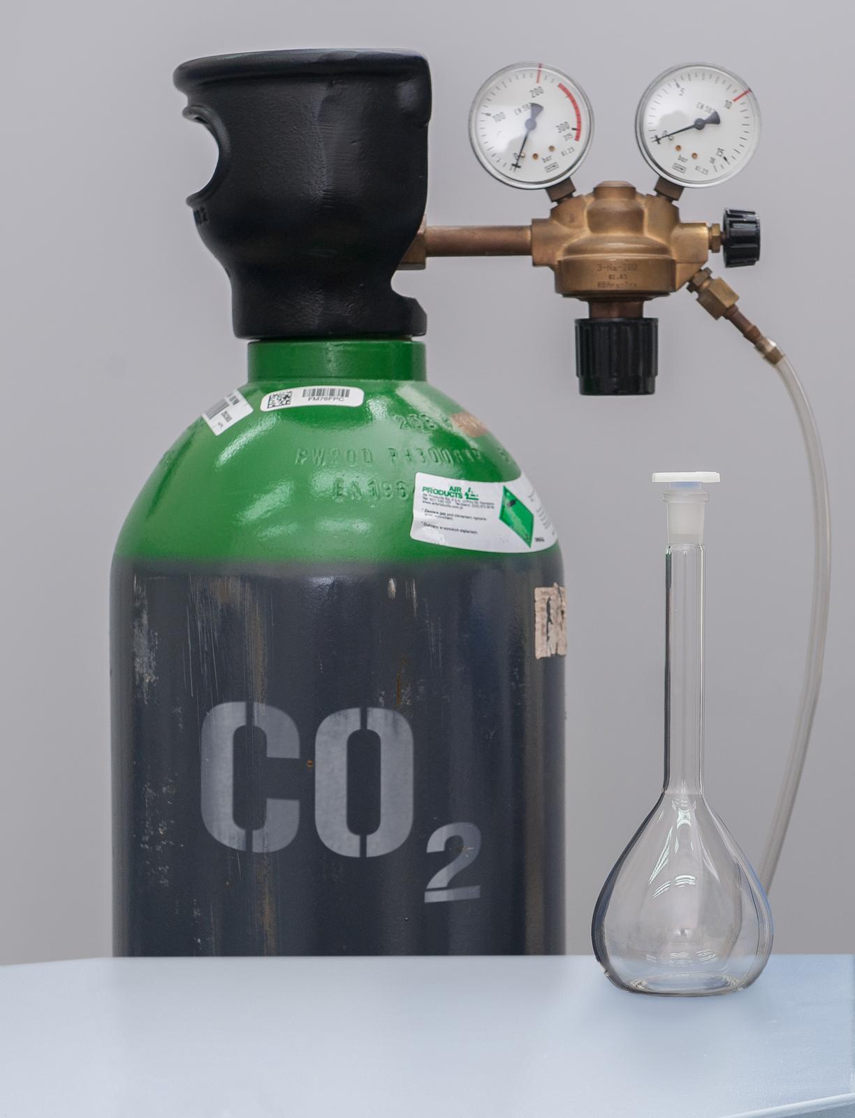 Zdjęcie przedstawia stolik zprzezroczystym zamkniętym naczyniem szklanym. Za nim stoi butla zgazem zaopatrzona wzawór opisana symbolem dwutlenku węgla CO2.