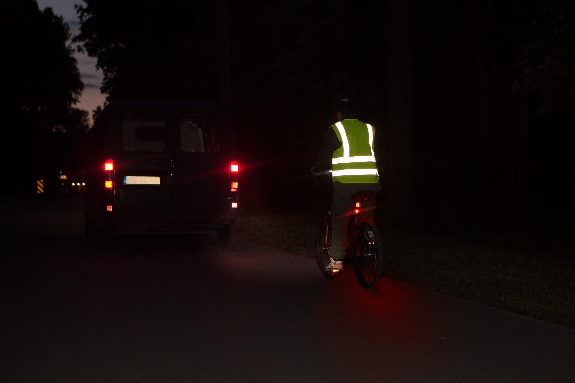 Rowerzysta nocą zelementami odblaskowymi, dobrze widoczny.
