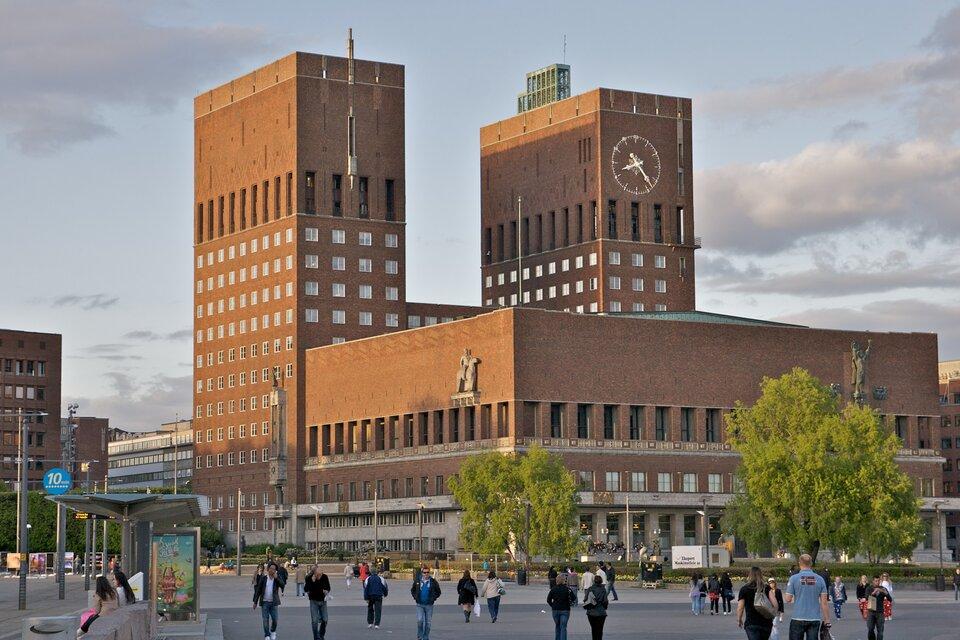 Na zdjęciu ceglasty budynek okształcie prostopadłościanu, odwóch wieżach. Liczne okna. Fasedę zdobią dwie płaskorzeźby. Na jednej zwież zegar. Przed budynkiem plac, przechodnie, przystanek komunikacji.