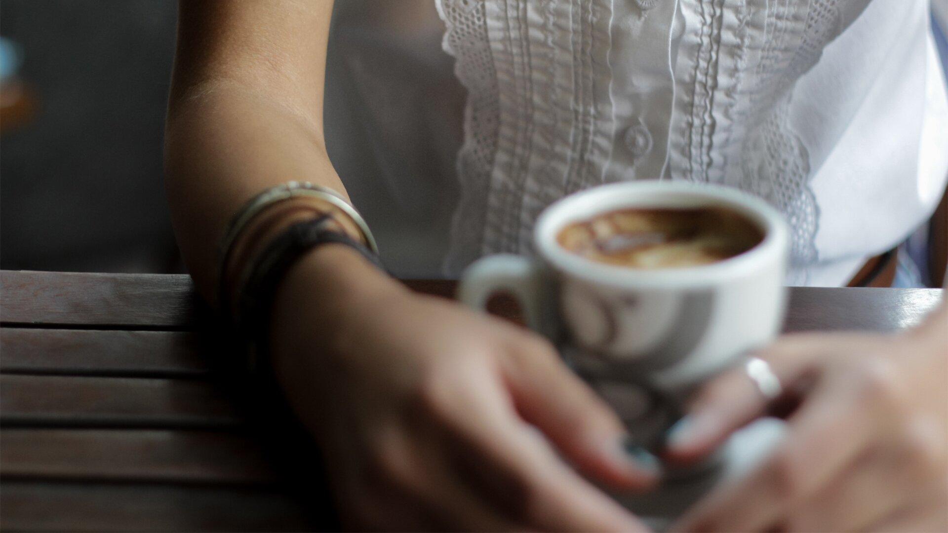 Zdjęcie przedstawia siedzącą przy stole kobietę wbiałej bluzce. Widoczny jest fragment torsu ispoczywające na stole ręce. Na stole przed siedzącą kobietą stoi filiżanka zkawą.