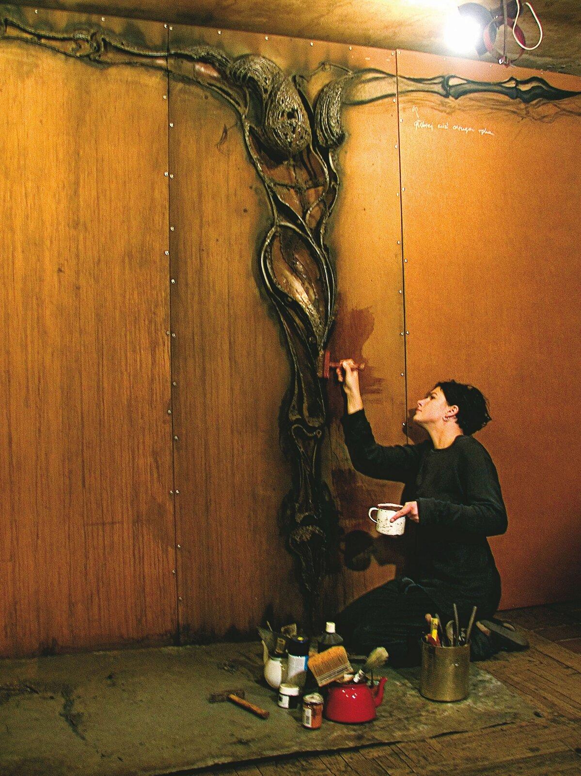 """Ilustracja przedstawia Annę Wysocką wtrakcie pracy nad instalacją """"Bez tytułu"""". Na zdjęciu ukazana jest artystka malująca znajdującą się na pomarańczowej płaszczyźnie, rzeźbę przypominającą postać zrozpostartymi ramionami, bez głowy. Kobieta klęczy na ziemi, wprawej ręce trzyma czerwony, szeroki pędzel, natomiast wlewej biały kubek. Ubrana jest wczarny kombinezon. Na ziemi stoją pojemniki zpędzlami ifarby wsłoiczkach, obok nich leży młotek. Miejsce pracy oświetlone jest zwisającą zgóry lampą."""