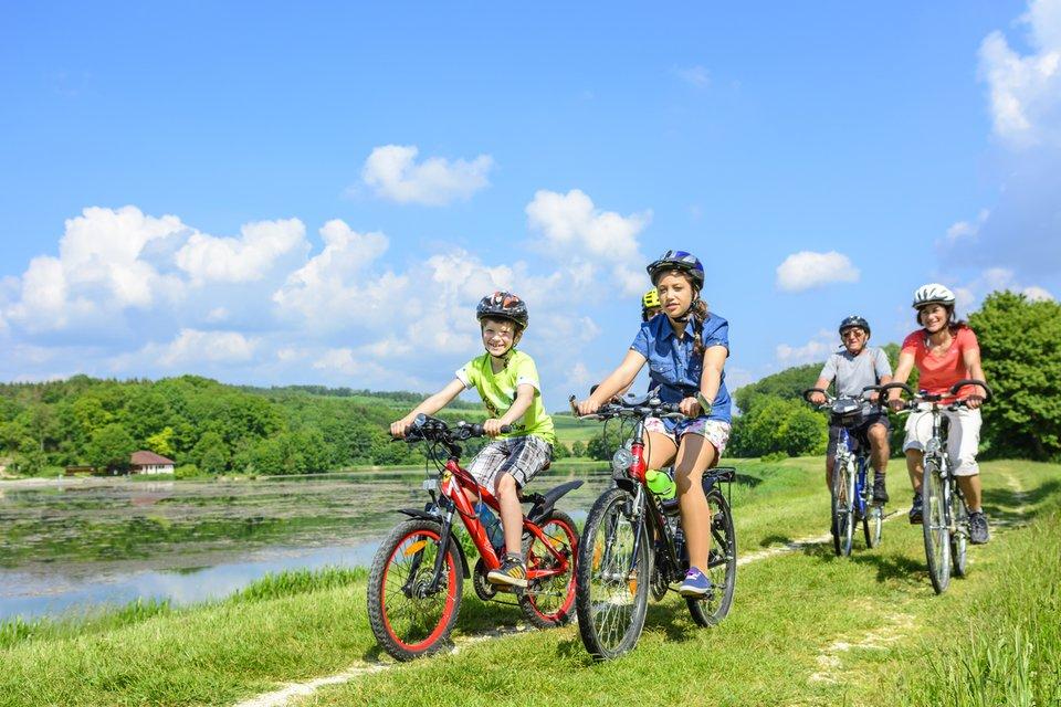 Fotografia przedstawia grupę pięciu osób jadących na rowerach.Na pierwszym planie kilkunastoletni chłopiec ikilkunastoletnia dziewczynka. Za nimi trzy osoby starsze. Uśmiechnięci rowerzyści, wyposażeni wkaski rowerowe iubrani wsposób właściwy dla pory letniej, poruszają się po polnej drodze, wzdłuż zbiornika wodnego. Wdali iwokół rowerzystów roztacza się słoneczny krajobraz, drzewa pokryte mnóstwem zielonych liści, trawa.