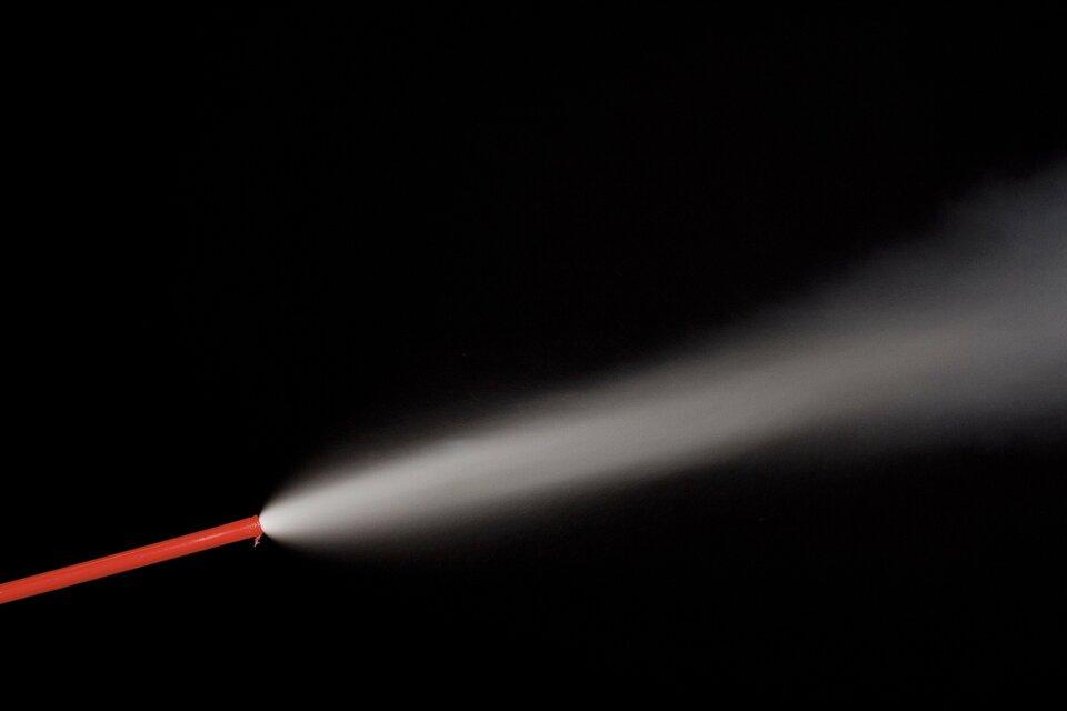 Ilustracja przedstawia strumień sprężonego powietrza wylatujący przez czerwoną rurkę dozownika. Na skutek gwałtownego obniżenia temperatury związanego zwymianą energii zotoczeniem podczas rozprężania strumień widoczny jest za sprawą skondensowanej pary wodnej. Tło zdjęcia czarne, rurka wlewej dolnej części kadru, strumień gazu biały uformowany ukośnie wpoprzek kadru.