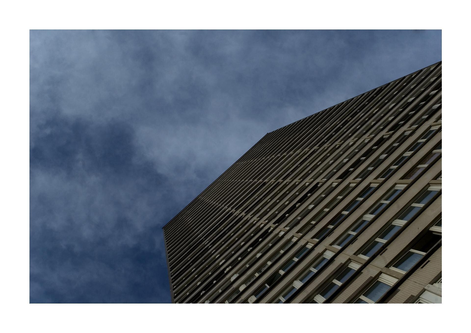 Wzadaniu zostało wykorzystane zdjęcie przedstawiające blok, kilkunasto piętrowy na błękitnym niebie.