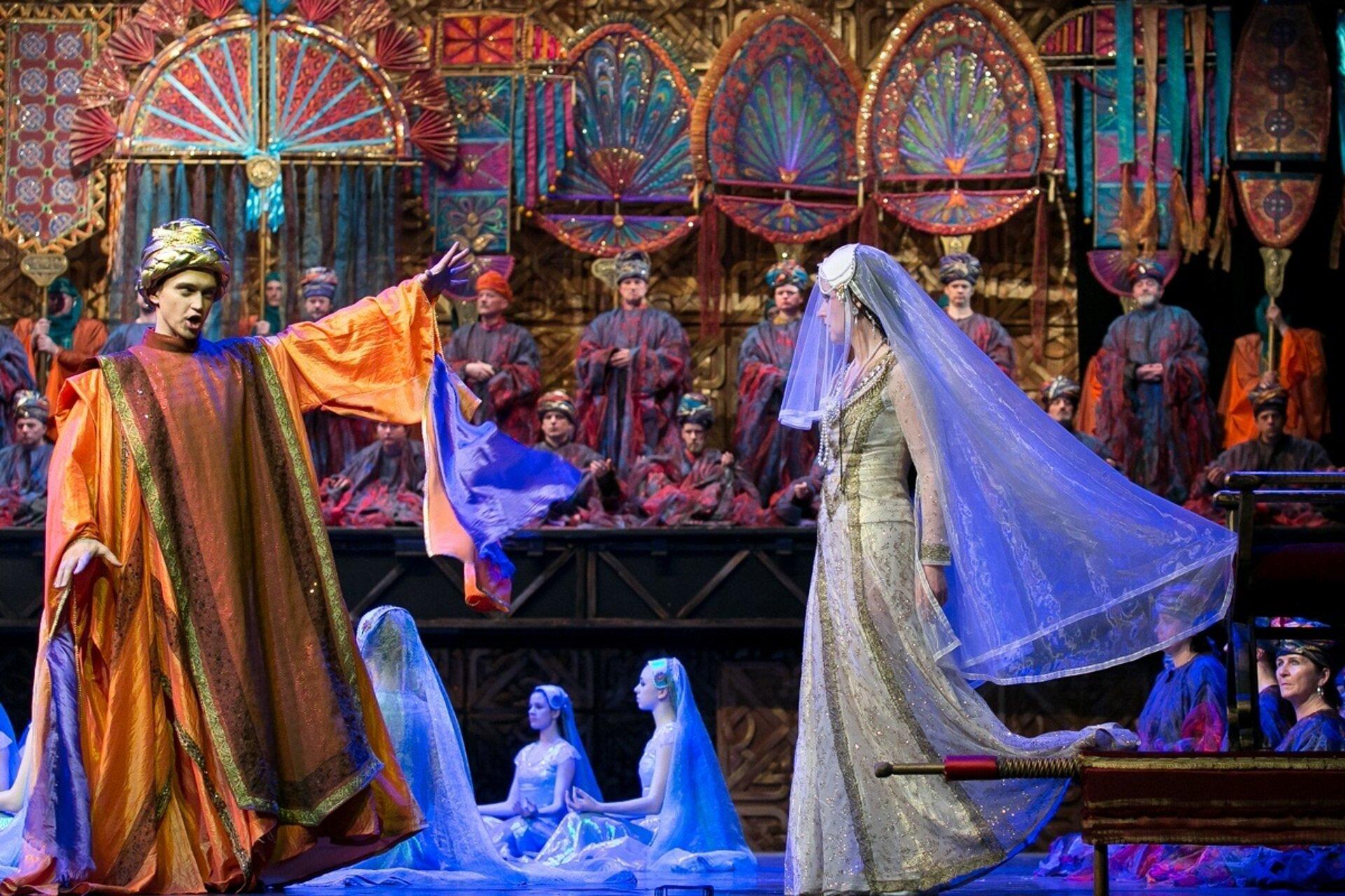"""Ilustracja przedstawia scenę zopery Georgesa Bizeta """"Poławiacze pereł"""". Akcja opery rozgrywa się na wyspie Cejlon. Na scenie widzimy kobietę wdługiej sukni oraz welonie. Na wprost niej znajduje się mężczyzna wpomarańczowej długiej sukni oraz turbanie na głowie. Dookoła sceny znajdują się inni aktorzy operowi."""