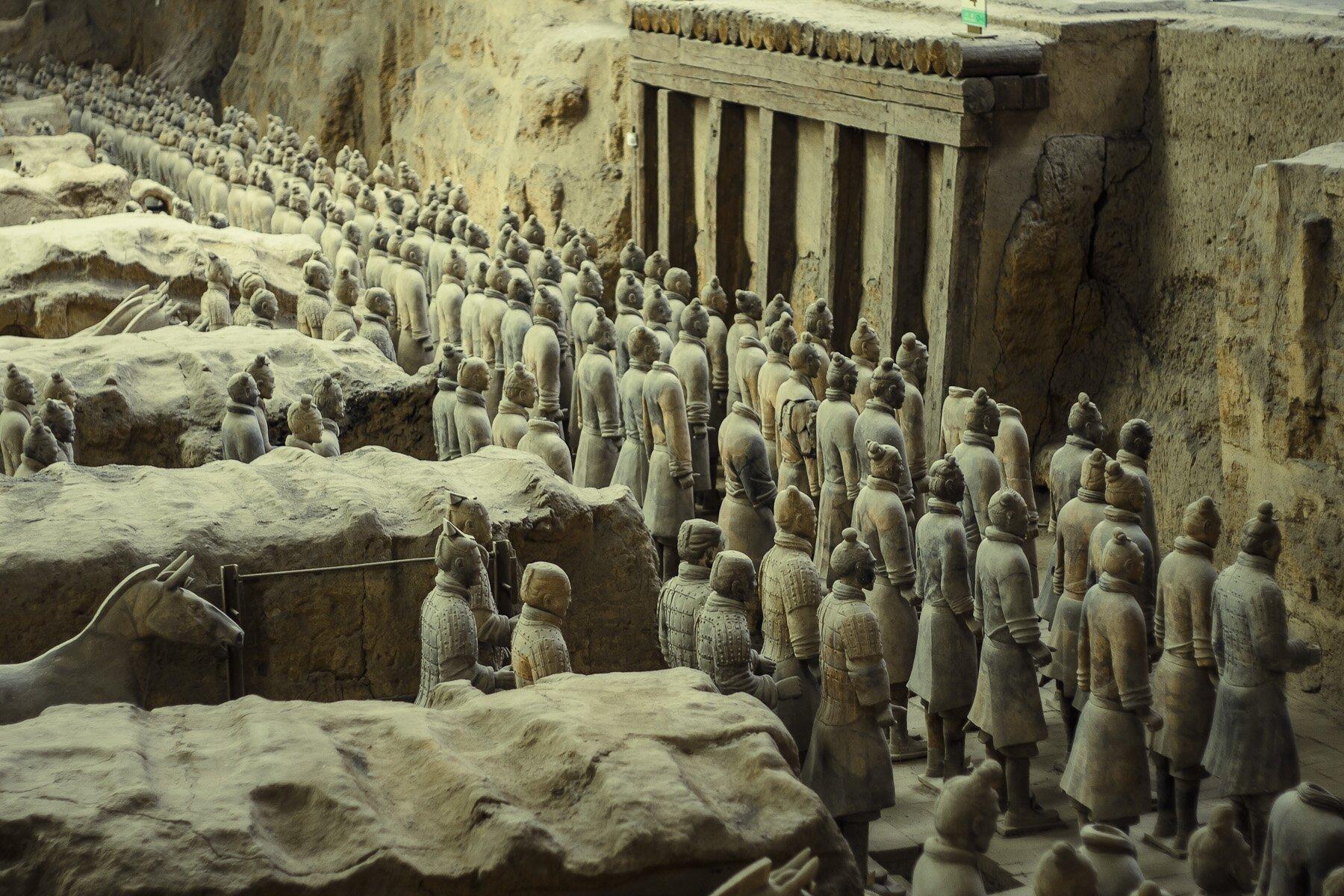 Fotografia przedstawia kamienne posągi żołnierzy chińskich stojących obok siebie. Między nimi widać kamienne bloki izwierzęta. Postacie stoją na przeciwko kamiennej ściany.