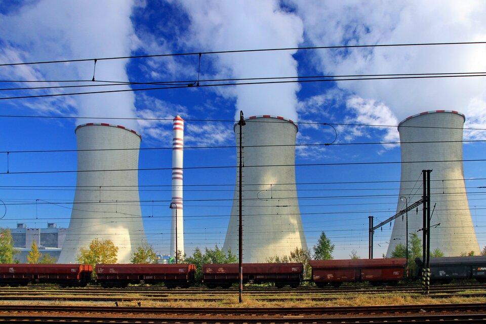 Fotografia prezentuje fragment elektrowni na węgiel kamienny. Widoczne trzy białe duże kominy, zktórych wydobywa się para wodna. Przed nimi tory kolejowe, którymi przejeżdża pociąg.