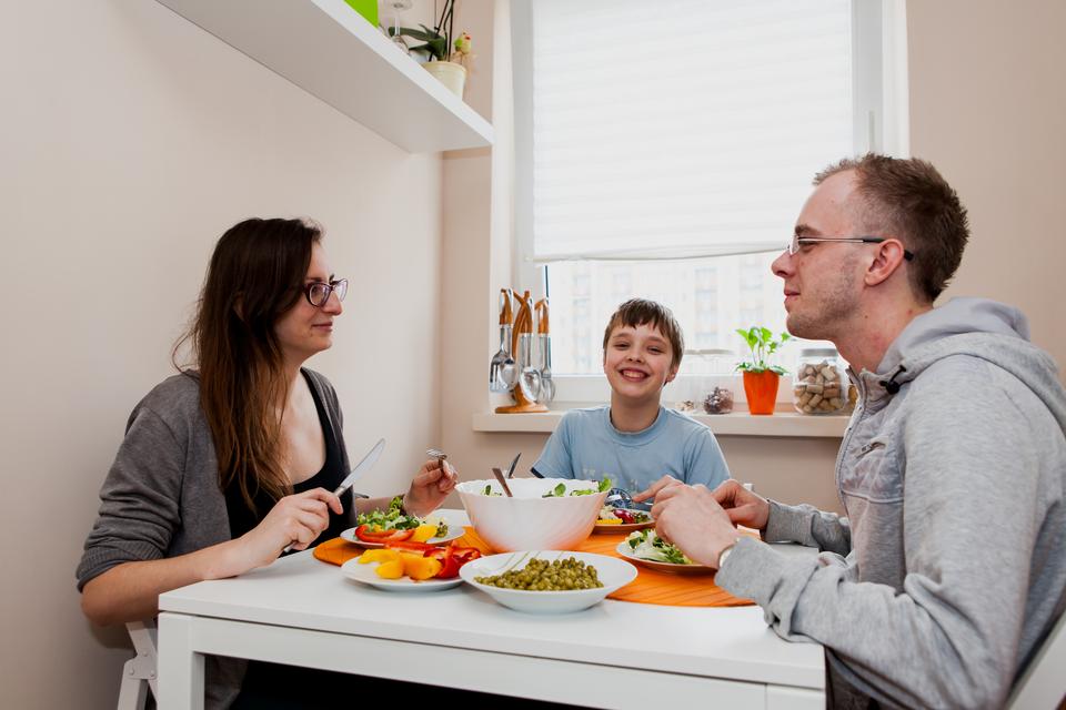 Fotografia przedstawiająca radosną rodzinę jedzącą zdrowy posiłek, pełen warzyw iowoców, bez produktów smażonych, pełnych tłuszczu.