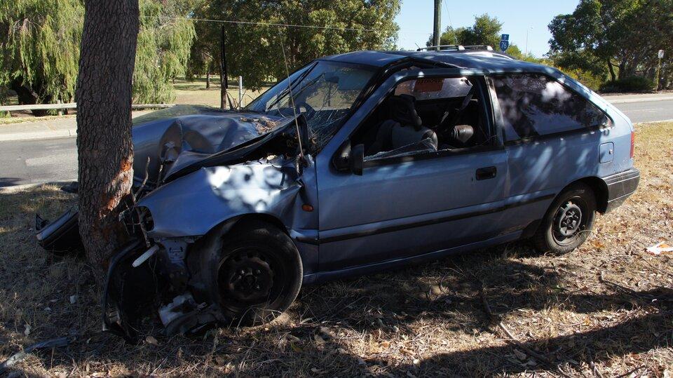Zdjęcie przedstawia samochód osobowy, który roztrzaskał się odrzewo. Na pierwszym planie pojazd bokiem do obserwatora, przód samochodu rozbity, wgnieciony wpień drzewa, pokrywa maski wygięta wgórę, nadkola zboku zdeformowane. Zderzak ireflektory zprzodu całkowicie zniszczone. Wsamochodzie nie ma nikogo. Okno od strony kierowcy bez szyby. Wtle asfaltowa droga idrzewa po drugiej stronie.