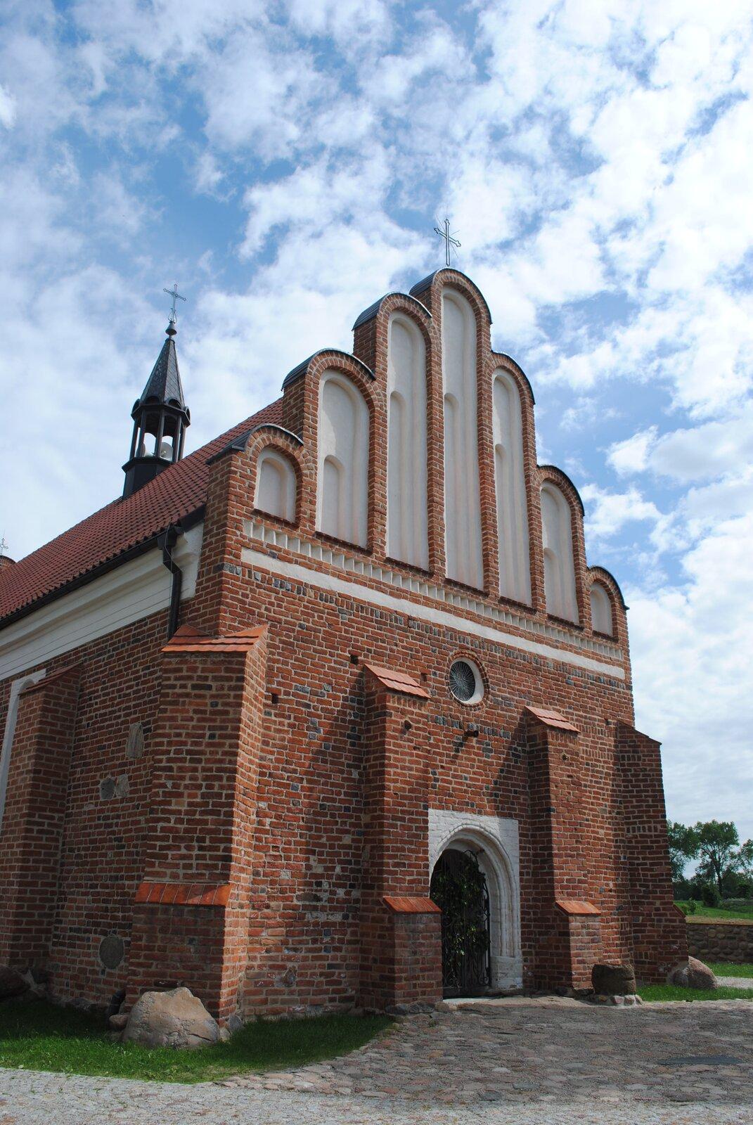 Kościół św. Stanisława wNiedźwiadnej.Murowanykościół wwiosce na północnym Podlasiu wybudowano dopiero około połowy XVI w. Wzory czerpane pobliskiego Księstwa Pruskiego (dawne ziemie zakonne) oraz samej Polski zadecydowały owzniesieniu go wtradycyjnej formie, zfasadą ozdobioną sterczynami, ale już proporcje kościoła (mała strzelistość), duże otwory okienne (na prezentowanym zdjęciu tego nie widać), półokrągłe zakończenie łuków fasady czy portalu (obramienia) wejścia uwidaczniają zachodzące zmiany. Kościół św. Stanisława wNiedźwiadnej.Murowanykościół wwiosce na północnym Podlasiu wybudowano dopiero około połowy XVI w. Wzory czerpane pobliskiego Księstwa Pruskiego (dawne ziemie zakonne) oraz samej Polski zadecydowały owzniesieniu go wtradycyjnej formie, zfasadą ozdobioną sterczynami, ale już proporcje kościoła (mała strzelistość), duże otwory okienne (na prezentowanym zdjęciu tego nie widać), półokrągłe zakończenie łuków fasady czy portalu (obramienia) wejścia uwidaczniają zachodzące zmiany. Źródło: Rafał Zarzecki, Wikimedia Commons, licencja: CC BY-SA 3.0.