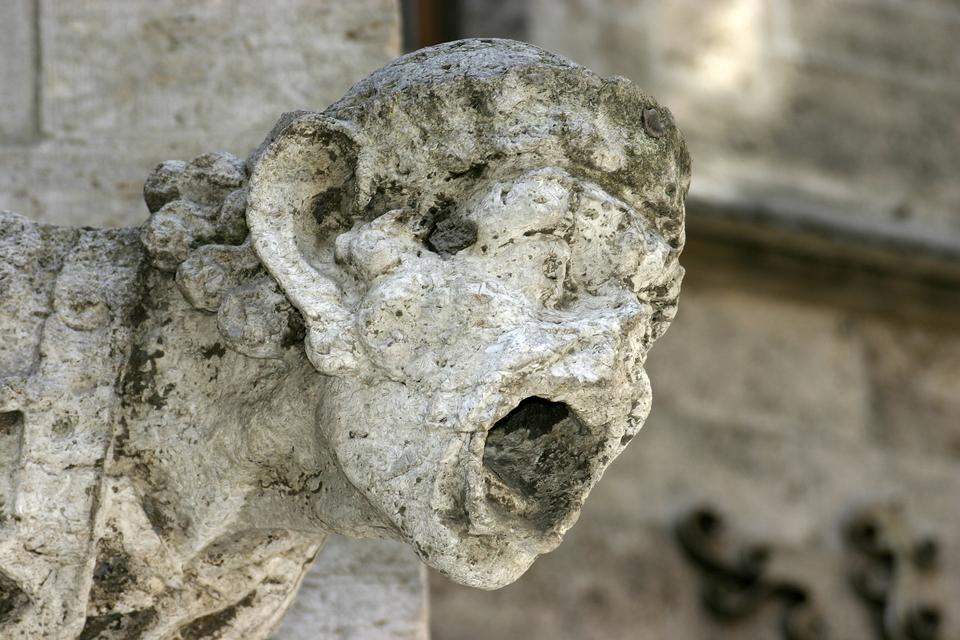 Fotografia prezentuje zniszczoną rzeźbę głowy umieszczoną na budynku.