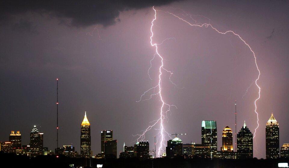 Fotografia przedstawia miasto nocą podczas burzy. Na fotografii ujęto moment uderzenia pioruna, któremu towarzyszy zjawisko świetlne onierównomiernym kształcie. Podczas burz nie wolno chować się przed deszczem pod drzewami iinnymi wysokimi przedmiotami.