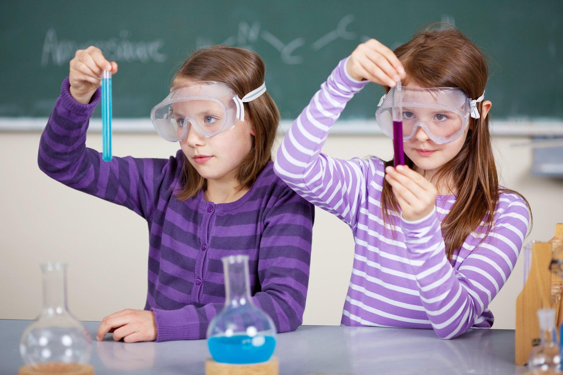 Fotografia przedstawia dwie uczennice wpracowni przyrodniczej. Dziewczynki siedzą przy stole iprzeprowadzają doświadczenie. Mają na sobie ochronne gogle, awrękach trzymają próbówki. Jedna próbówka wypełniona jest fioletowym płynem, adruga niebieskim. Przed uczennicami znajdują się szklane kolby laboratoryjne. Za plecami uczennic, na ścianie, wisi tablica, na której zapisano wzory chemiczne.