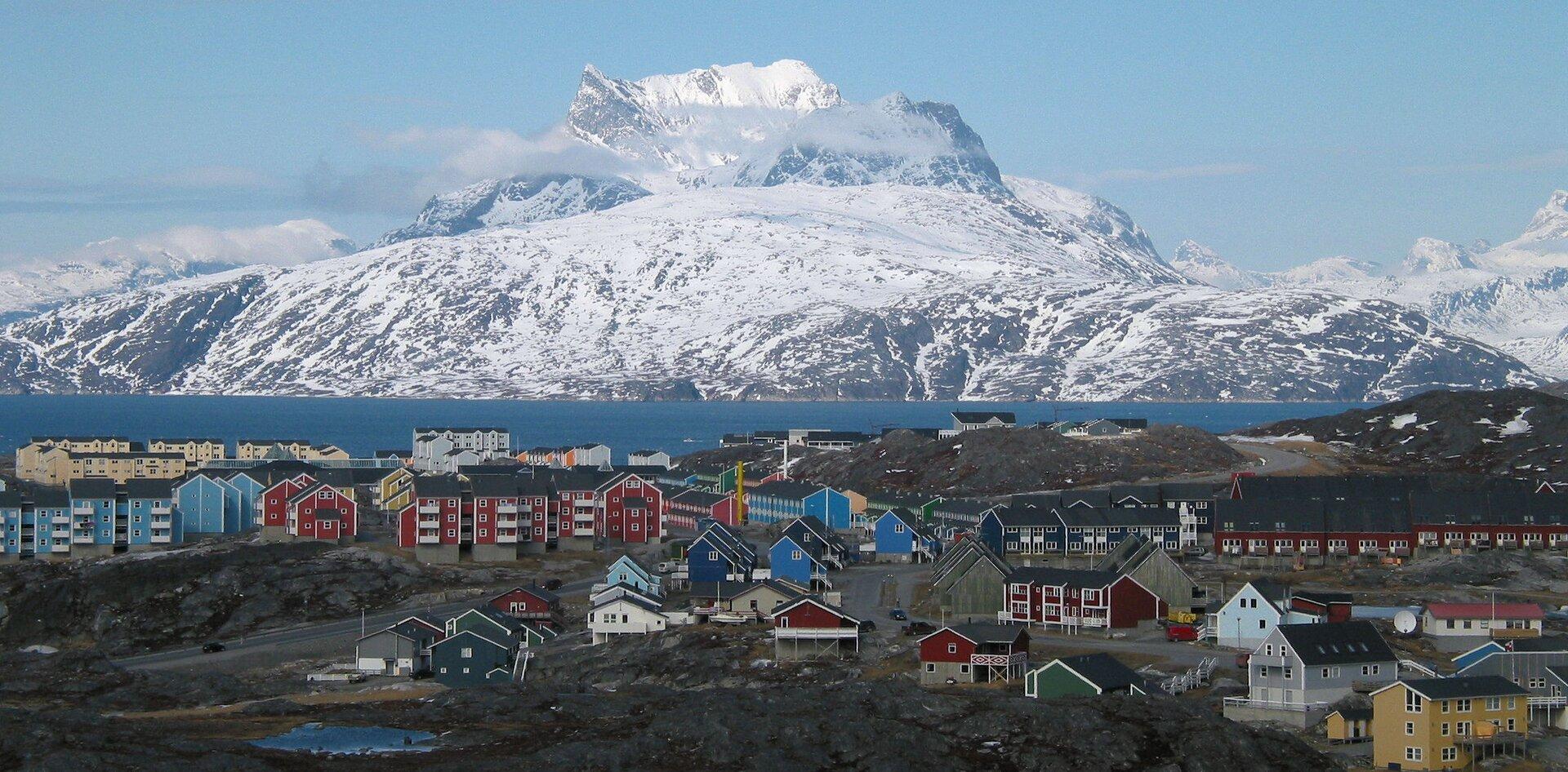 Na zdjęciu zabudowania na brzegu morza, kolorowe domy, spadziste dachy. Brak roślinności. Wtle na drugim brzegu skalisty, ośnieżony szczyt.