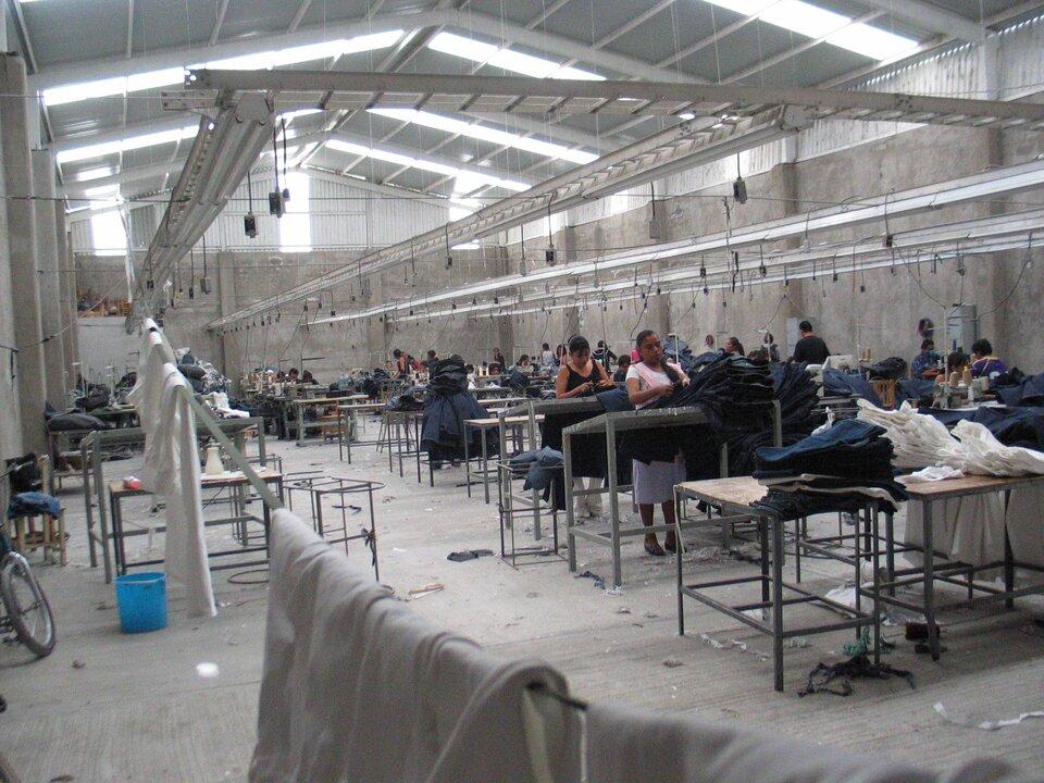 Na zdjęciu szwalnia odzieży. Wwysokiej betonowej hali rzędy wysokich stołów. Pod sufitem oświetlenie. Na stołach tkaniny dżinsowe ibiałe. Kobiety stoją przy stołach iskładają produkty. Wtle niższe stoły, maszyny do szycia, szwaczki szyją.
