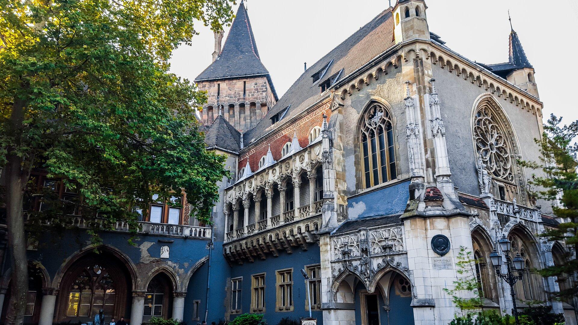 Ilustracja przedstawia Zamek Vajdahunyad wBudapeszcie. Niebiesko-szare ściany przyozdobione są bogatymi elementami ornamentów architektonicznych. Zamek posiada także liczne okna.