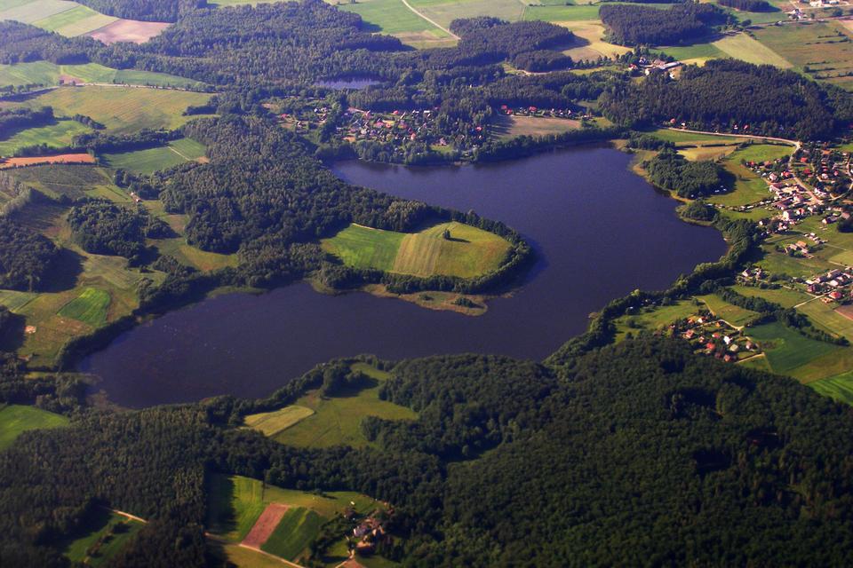 Fotografia wykonana zlotu ptaka ukazuje jeziora Pojezierza Pomorskiego. Wokół jeziora liczne lasy oraz łąki ipola.