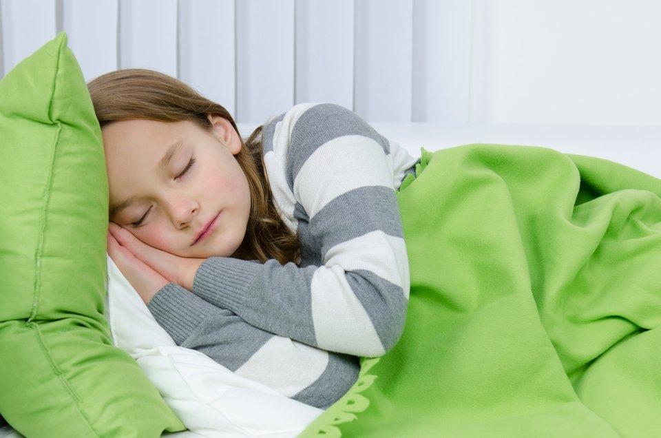 Fotografia przedstawia śpiącą dziewczynkę. Dziewczynka odpoczywa włóżku, leży na prawym boku, opierając głowę na złożonych dłoniach wsuniętych pod prawy policzek. Jest przykryta zielonym kocem.
