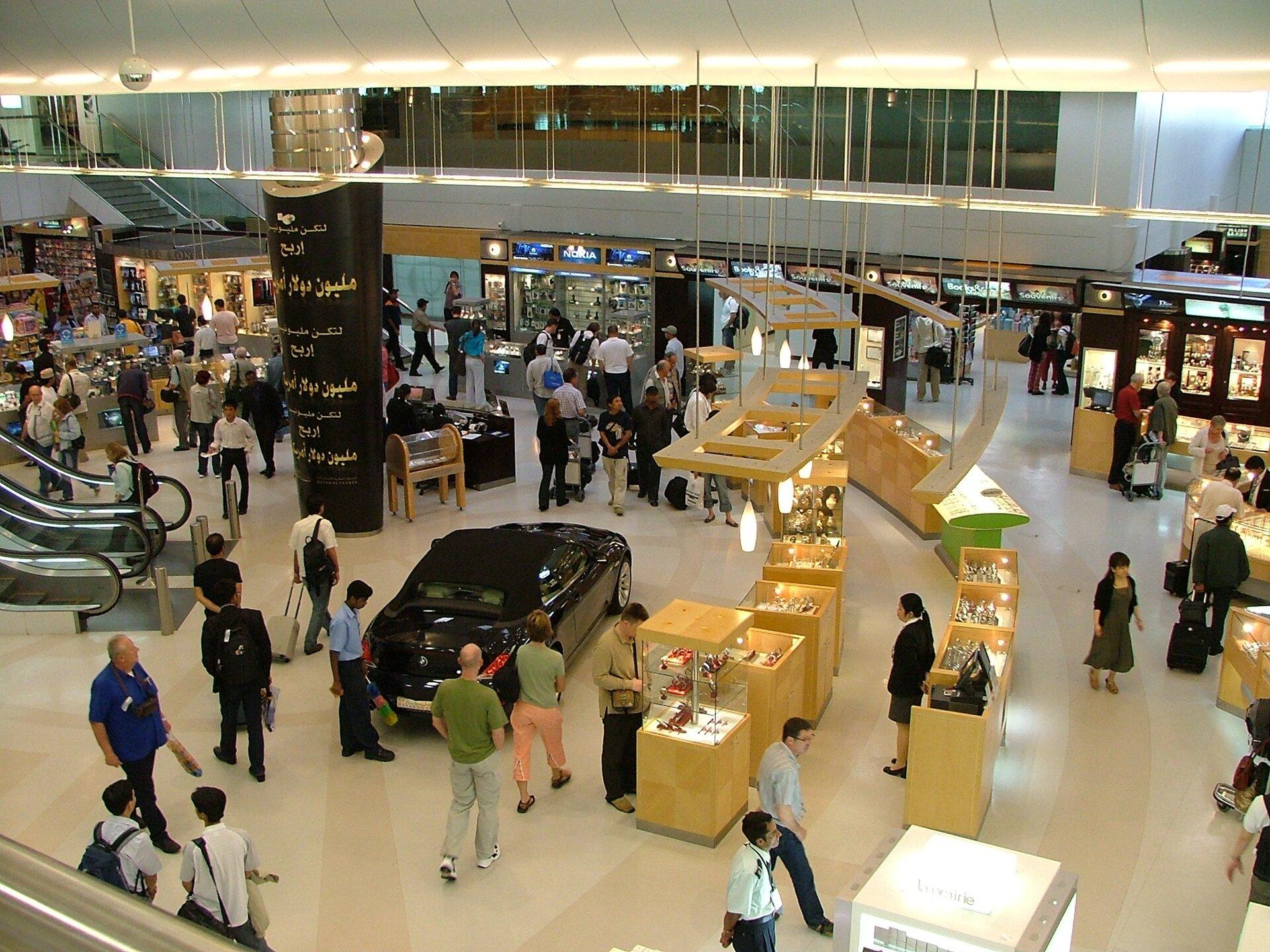 Na zdjęciu nowoczesna galeria handlowa, witryny sklepowe, stoiska, ruchome schody, klienci.