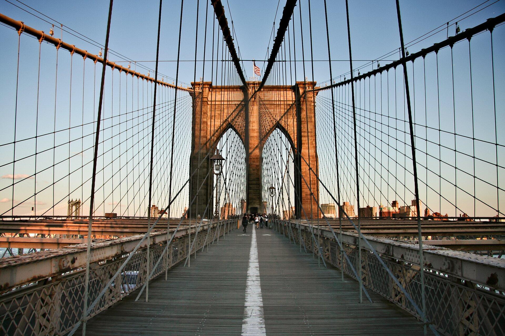 Ilustracja przedstawia Most Brookliński wNowym Jorku. Na zdjęciu ujęcie przy wejściu na most. Wcentralnej części widać filar mostu oparty na trzech kolumnach. Na szczycie zatknięta jest flaga USA. Zfilaru odchodzą liny trzymające konstrukcję mostu. Powierzchnia mostu wyłożona jest deskami iwidać idących po nim ludzi. Po obu stronach są metalowe grube barierki zsiatką. Woddali widać budynki miasta iniebieskie niebo.