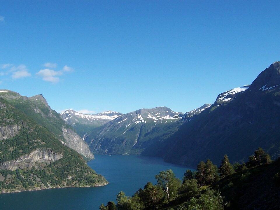 Na zdjęciu pasmo górskie, stoki porośnięte lasami, szczyty ośnieżone, wdolinie zbiornik wodny.