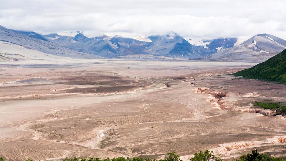 Na zdjęciu na pierwszym planie płaski teren pokryty grubą warstwą brązowego pyłu. Pęknięcia izagłębienia. Wtle wysokie góry wnajwyższych partiach pokryte śniegiem. Szczyty gór wchmurach. Chmury gęste. Nie widać nieba.