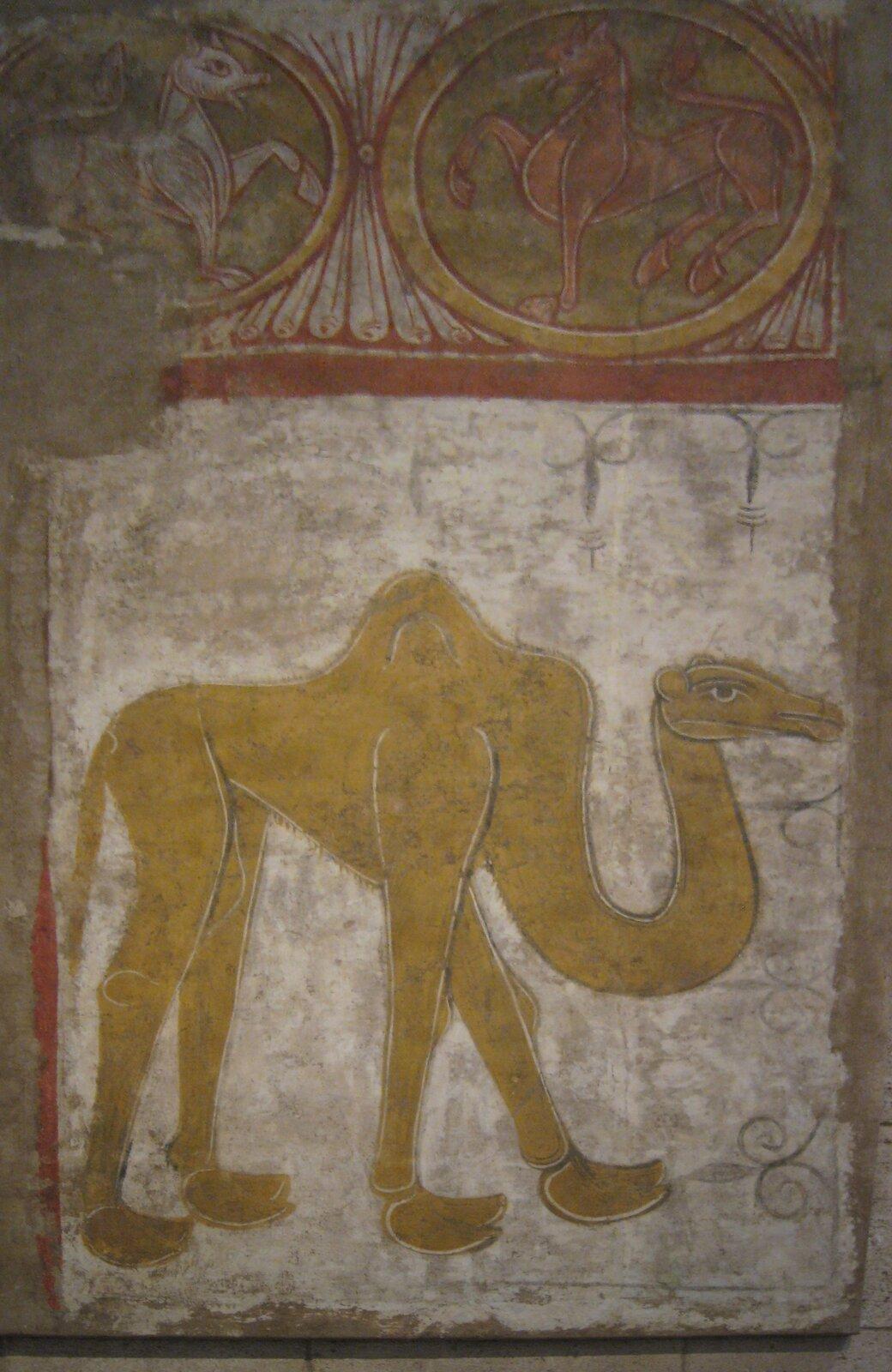 """Ilustracja przedstawia malowidło """"Wielbłąd"""". Fresk naścienny przedstawia postać żółtego wielbłąda na białym tle. Namalowany jest wbardzo uproszczonej formie, płaską plamą idelikatnym konturem. Nad nim znajduje się fragment czerwono-białego ornamentu zdwoma okręgami wktórych umieszczono postacie zwierząt zkopytami iogonem. Zwierzę po lewej stronie malowidła jest białe, zwierzę po prawej brązowe."""