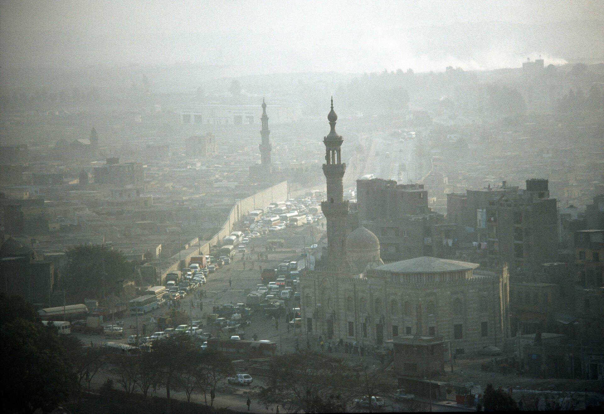 Zdjęcie przedstawia oglądane zpobliskiego wzgórza lub wysokiego budynku miasto spowite smogiem. Uwagę zwraca mała przejrzystość powietrza, promienie słońca ztrudem przebijające się przez zanieczyszczenia, duża liczba samochodów na ulicach oraz dym unoszący się zdzielnic położonych wtle. Na pierwszym planie szeroka aleja wiodąca wgłąb kadru izabytkowe budynki zwysokimi wieżami stojące przy niej.
