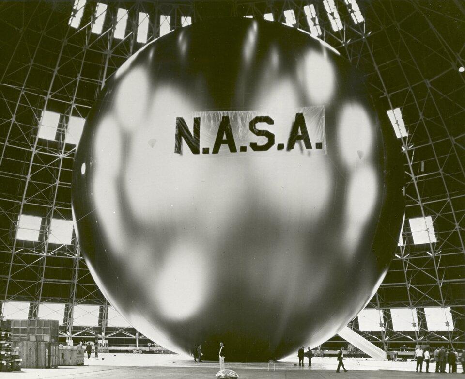 """Zdjęcie przedstawia satelitę Echo 1. Zdjęcie czarno-białe. Na zdjęciu widoczna ogromna, srebrna kula. Kula wypełnia całe zdjęcie. Wtle rusztowania oraz lampy oświetlające kulę. Na kuli znajduje się napis: """"N.A.S.A."""". Wpobliżu satelity znajduje się kilkanaście osób."""