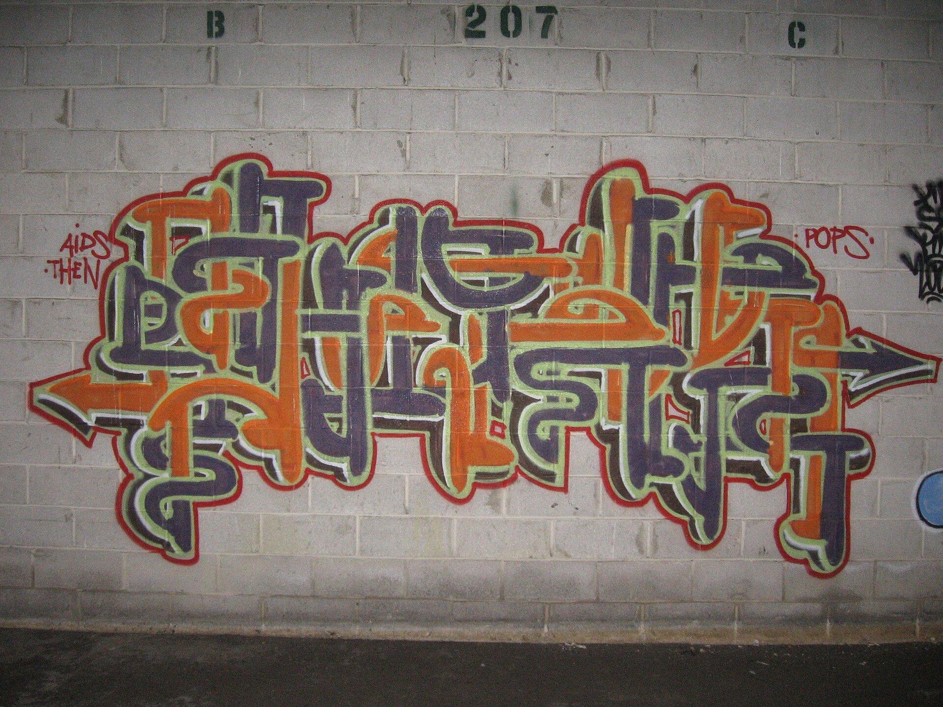 Zdjęcie przedstawia graffiti namalowane na jasnej ścianie. Ściana jest koloru białego. Graffiti namalowane jest wkolorze szarym oraz pomarańczowym.