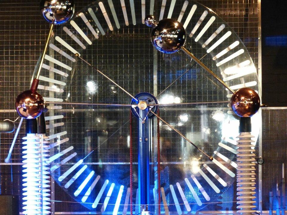 Zdjęcie przedstawia maszynę elektrostatyczną, której głównym elementem konstrukcyjnym są dwie sąsiadujące ze sobą obracające się tarcze. Na zdjęciu wykonane są one zprzezroczystego materiału, dzięki czemu dobrze widoczne są jedynie koncentrycznie ułożone wzdłuż krawędzi aluminiowe paski, które podczas obrotu tarcz wprzeciwnych kierunkach ulegają elektryzacji. Przed tarczami na ruchomych ramionach znajdują się metalowe kulki iskiernika, które można zbliżać lub oddalać od siebie.
