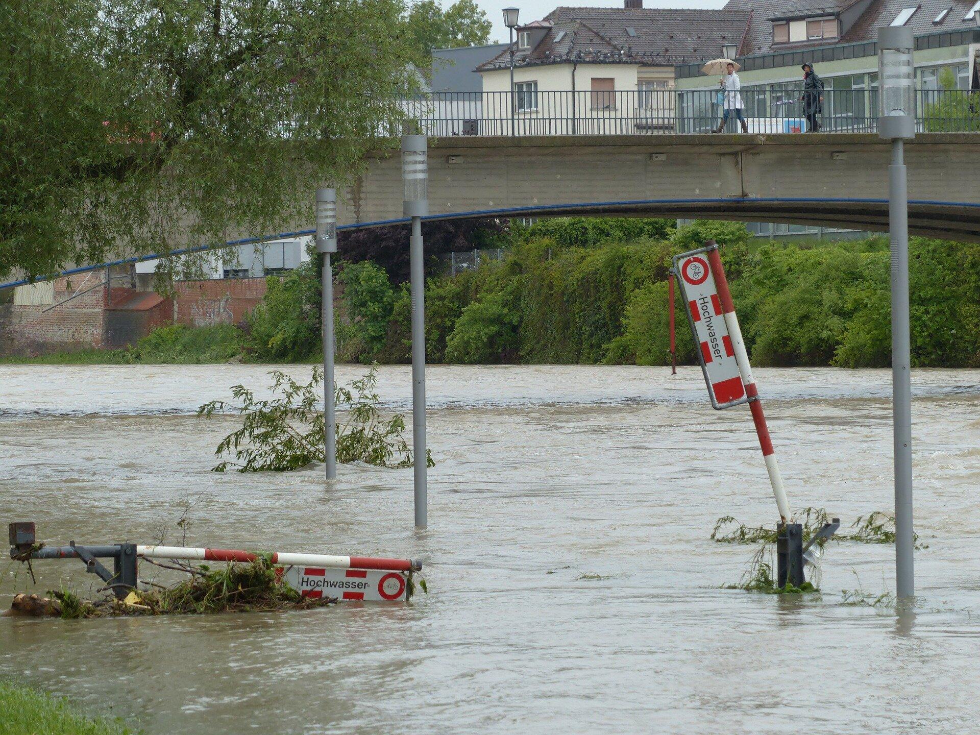 Zdjęcie przedstawia powódź wcentrum miasta. Deszczowy dzień. Na pierwszym planie koryto rzeki. Poziom wody sięga do połowy latarni wzdłuż brzegu rzeki. Na powierzchni unoszą się gałęzie drzew. Nad rzeką betonowy most. Wtle, na przeciwnym brzegu rzeki zabudowania miejskie.