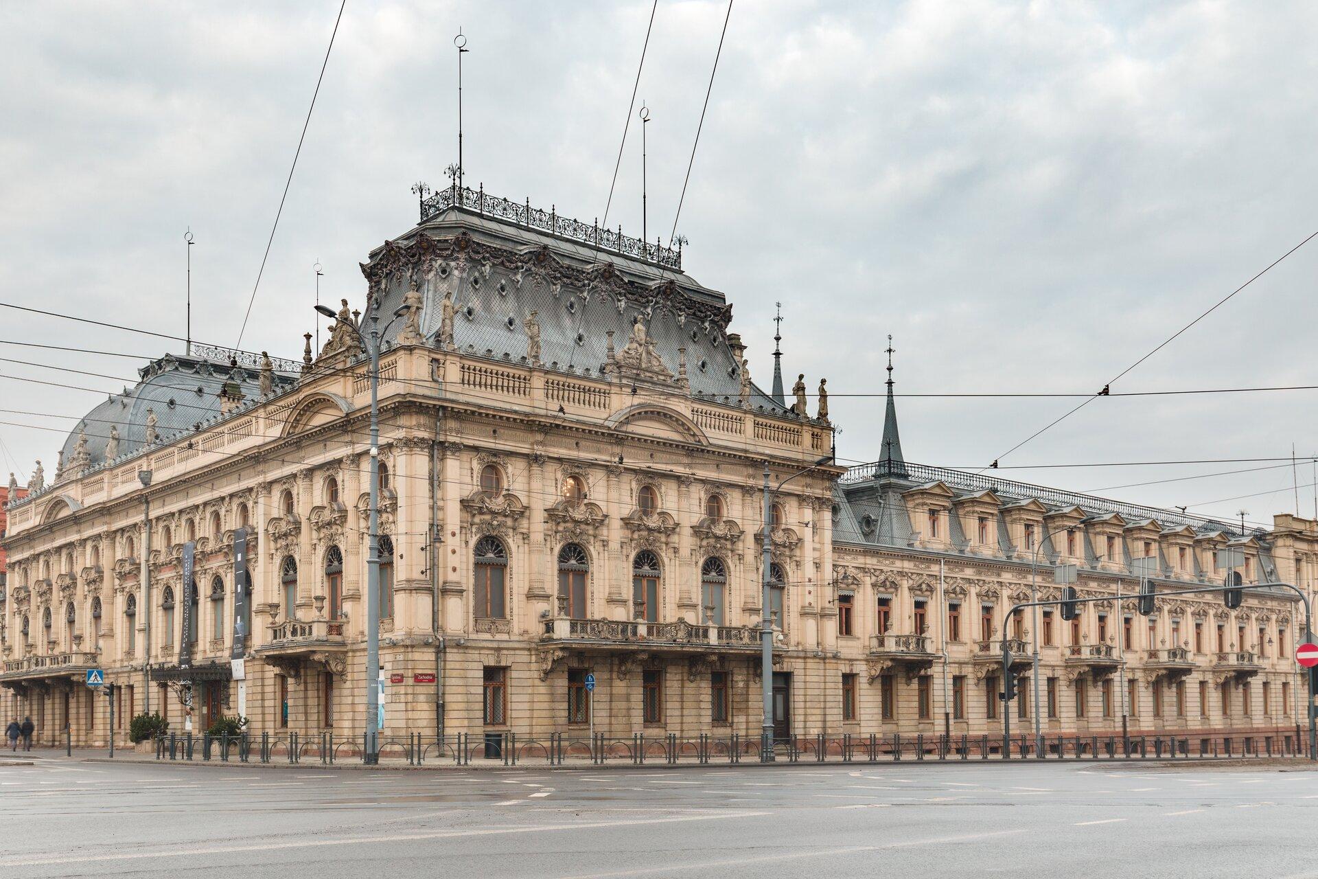 Ilustracja przedstawia pałac Izraela Poznańskiego wŁodzi. Budynek ten ma beżową elewację, oraz zielony dach, nad którym biegną linie telefoniczne.