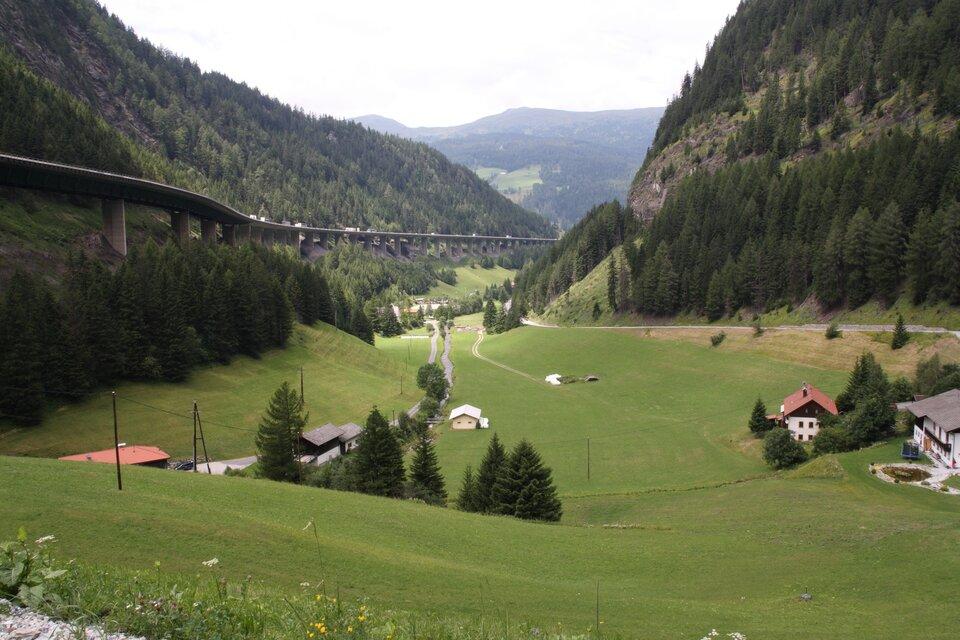 Na zdjęciu dolina, pojedyncze zabudowania, łąki. Zlewej strony wzdłuż stoku droga położona na wysokiej estakadzie.