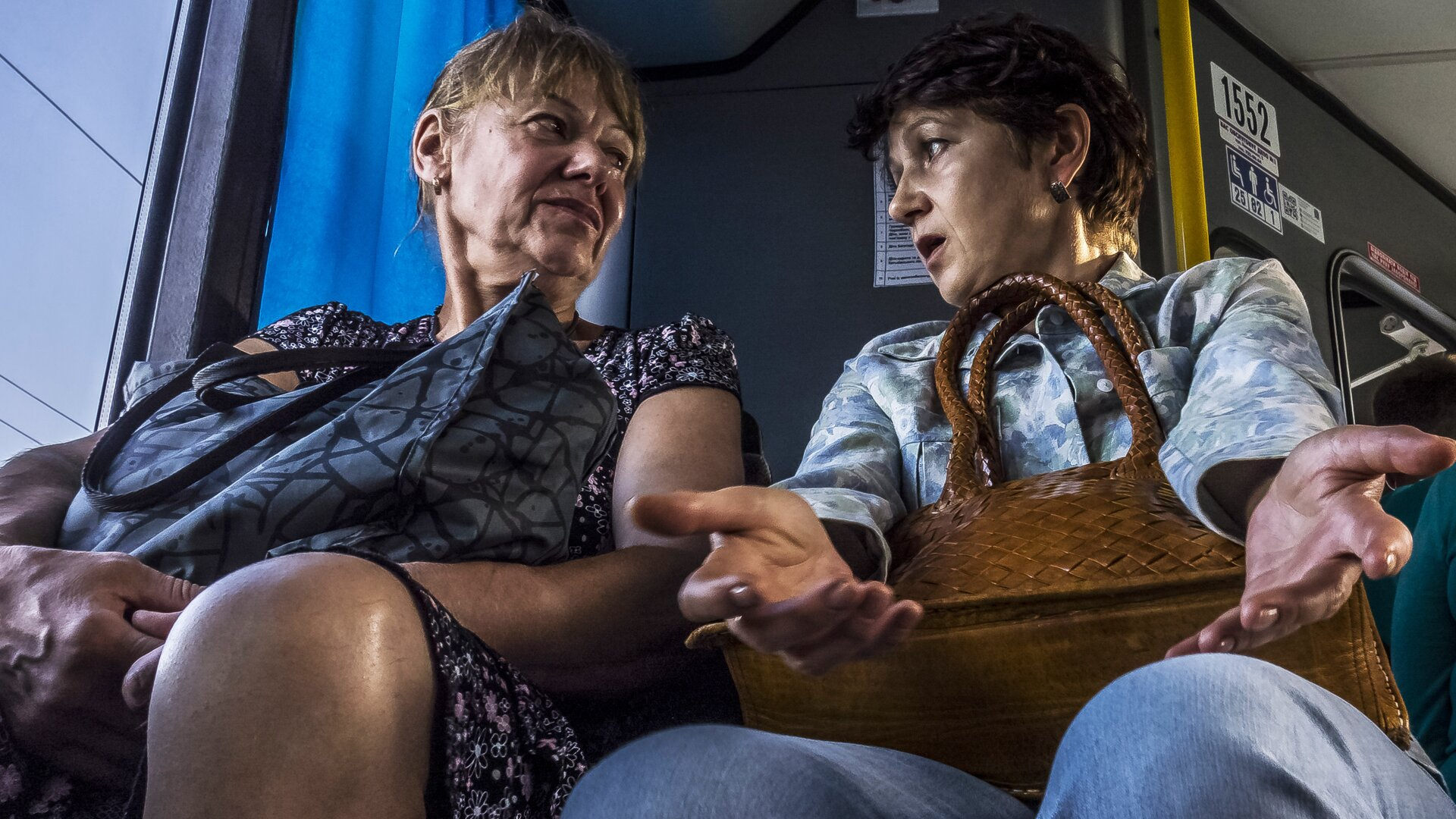 Zdjęcie przedstawia dwie kobiety, które ze sobą rozmawiają wautobusie. Obydwie trzymają na kolanach torebki. Jedna zkobiet ma otwarte usta igestykuluje. Druga słucha jej uważnie.