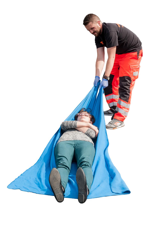 Galeria składa się zdziesięciu plansz przedstawiających sposoby przenoszenia poszkodowanego poza strefę zagrożenia. Na ilustracji numer pięć ratownik ubrany wpomarańczowo czarne spodnie zpaskami odblaskowymi poniżej kolan ciągnie poszkodowaną kobietę ułożoną na niebieskiej tkaninie. Kobieta leży na plecach, ręce ma złożone na klatce piersiowej.
