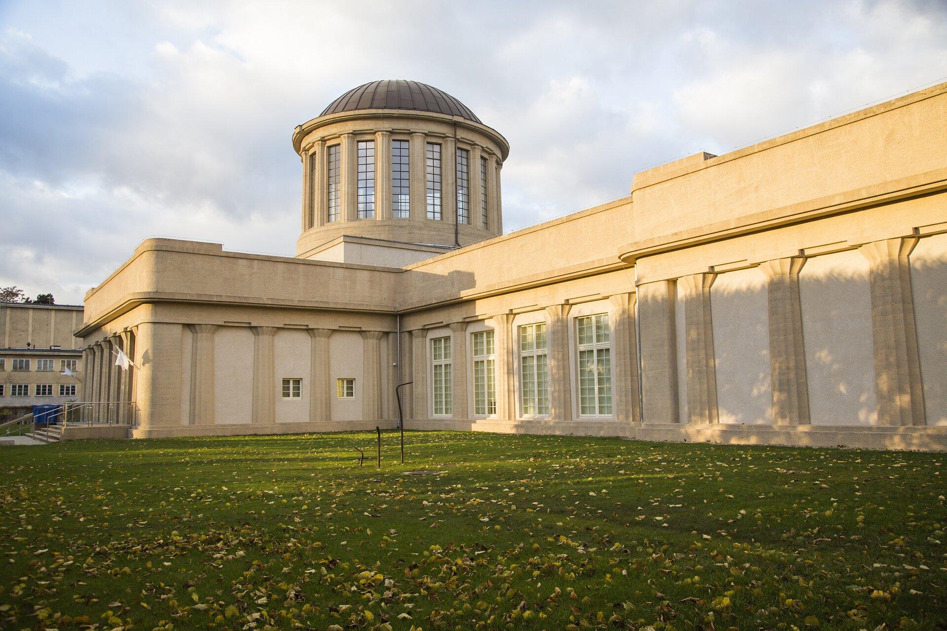 Ilustracja przedstawia Pawilon Czterech Kopuł, oddział Muzeum Narodowego we Wrocławiu - widok zzewnątrz. Budynek jest koloru beżowego. Jest to niski budynek otoczony trawnikiem. Zlewej części ilustracji widać schody po których się wchodzi do środka. Wcentrum widać sześć okien (cztery duże idwa małe). Nad budynkiem wznosi się wysoka wieża zakończona kopułą. Zbudowana jest ona zmurowanych słupów, miedzy którymi umieszczone są okna.
