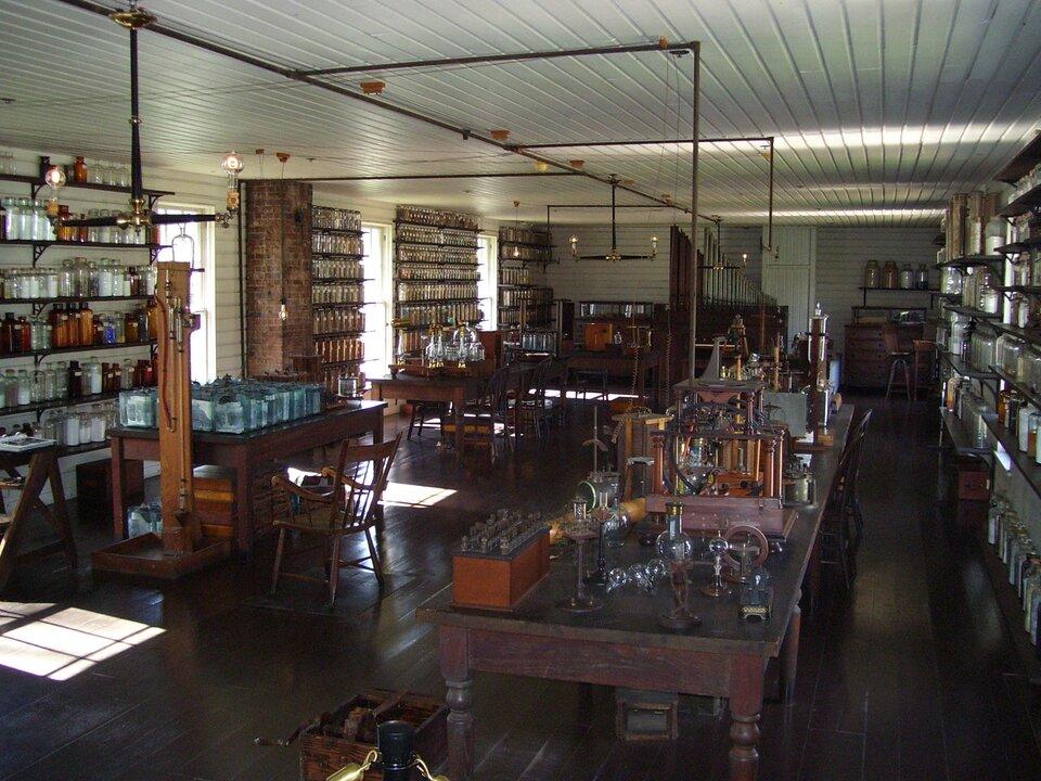 Na zdjęciu wnętrze zabytkowego laboratorium, drewniane stoły, na nich probówki inaczynia. Na półkach wsłoikach kolorowe substancje.