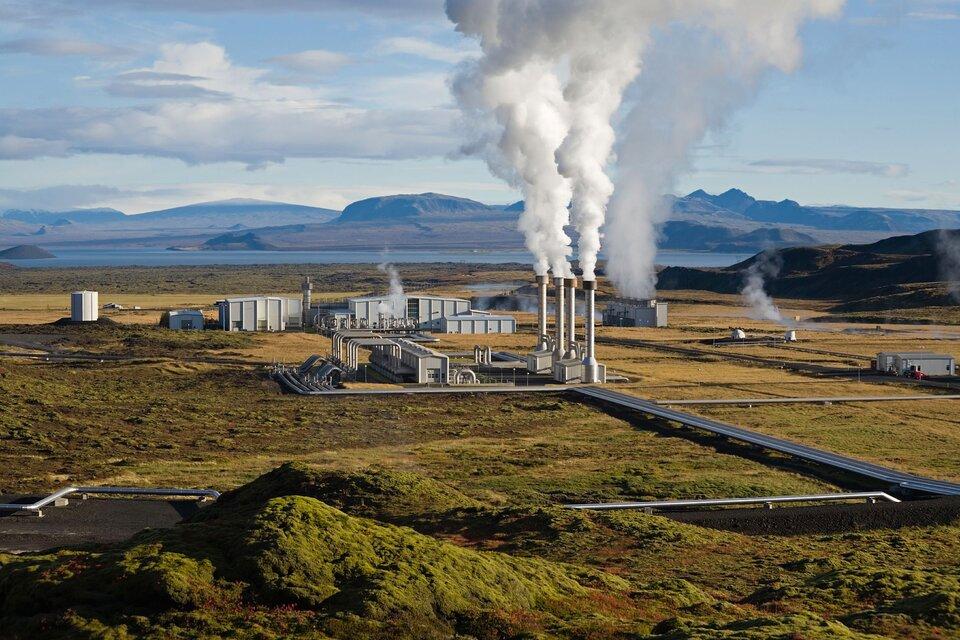 Fotografia przedstawia zdaleka zabudowania przemysłowe wgórzystym krajobrazie. Za nimi zbiornik wodny, na pierwszym planie zwały ziemi. Wokół zakładu jest pusto. Ztrzech wysokich, białych kominów ulatniają się kłęby pary wodnej. Zmniejszych kominów unosi się biały dym.