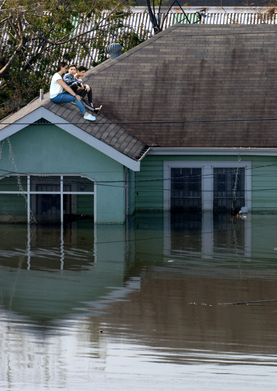 Kolorowe zdjęcie przedstawia powodzian ratujących się na dachu zalanego domu. Dzień. Zdjęcie przedstawia zalany dom. Woda sięga do poddasza. Mieszkańcy domu, 3 osoby, siedzą na spadzistym dachu.