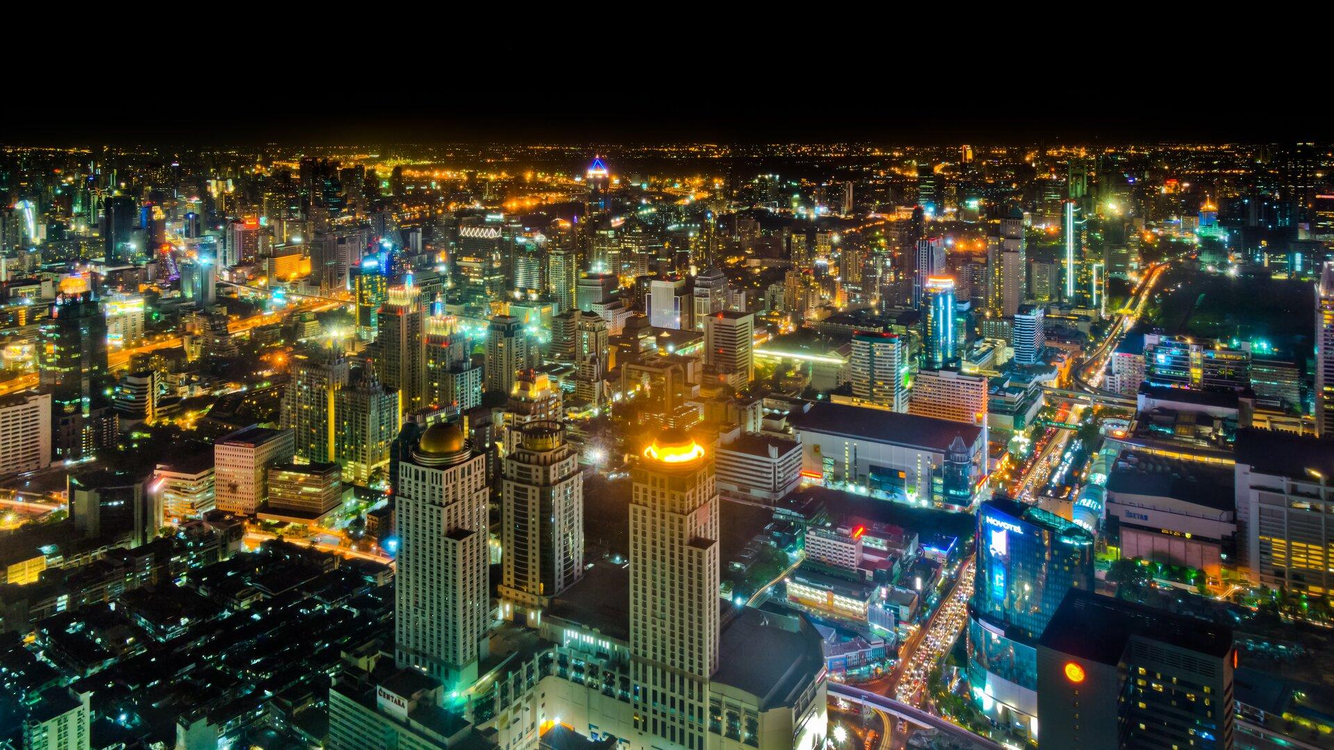 Na zdjęciu panoramicznym nowoczesna zabudowa. Noc, kolorowe światła.